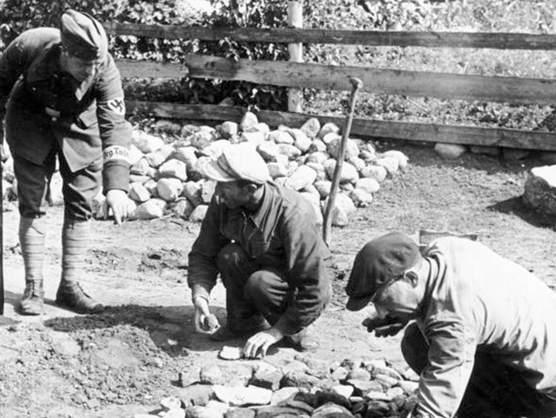Ein Mann der Organisation Todt bewacht die Arbeit der KZ-Häftlinge für die Rüstungsbunker