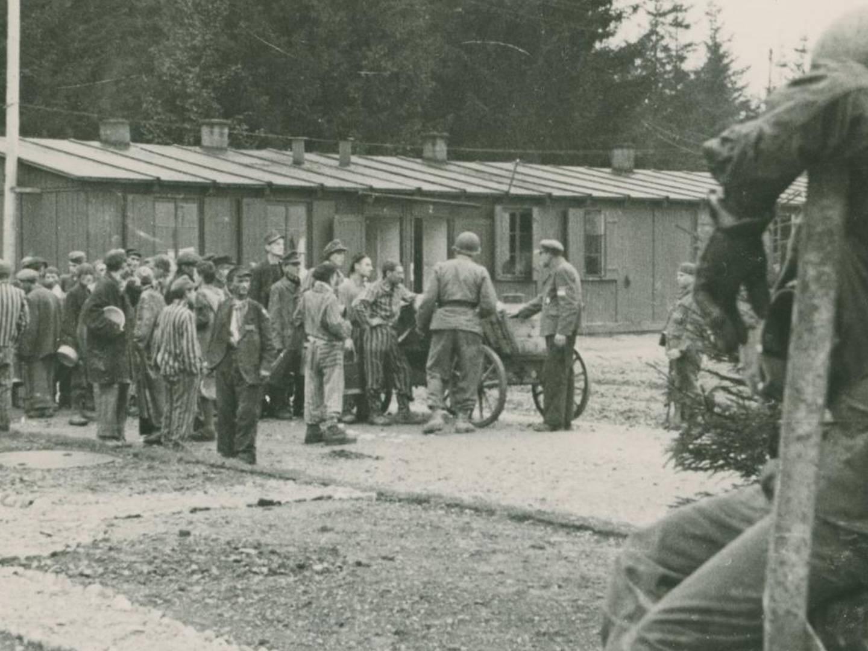 US-amerikanische Soldaten und befreite KZ-Häftlinge vor SS-Baracken am Lager Kaufering I.